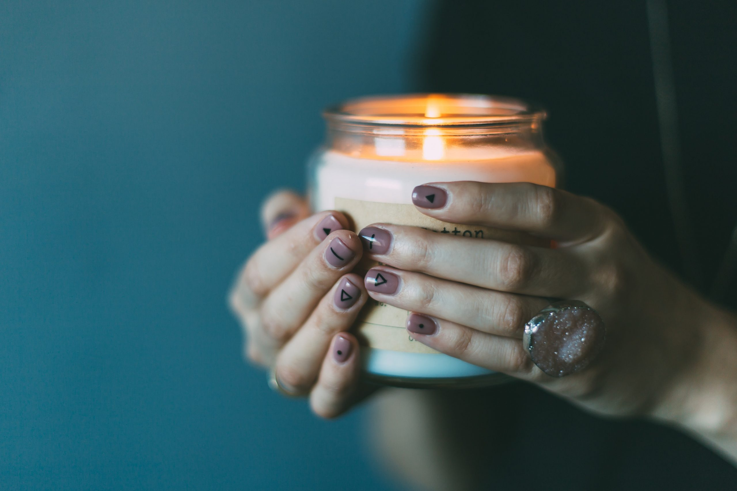 Woman's hands holding a jar candle that is lit.