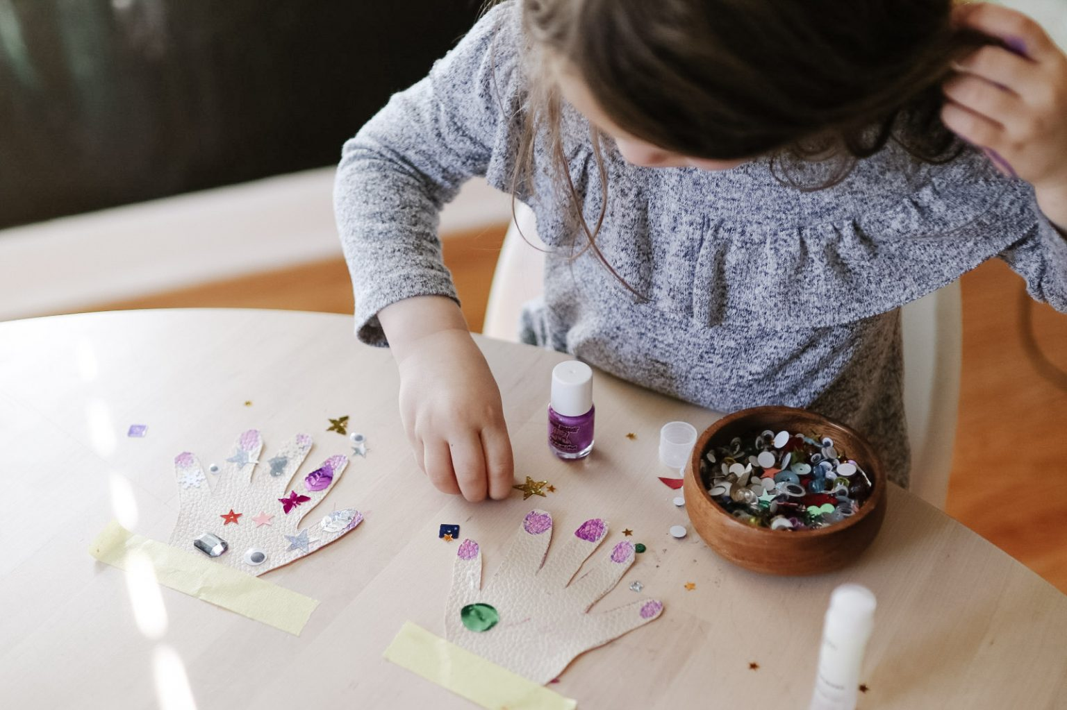 Girl finding things to do at home with kids and doing a craft.