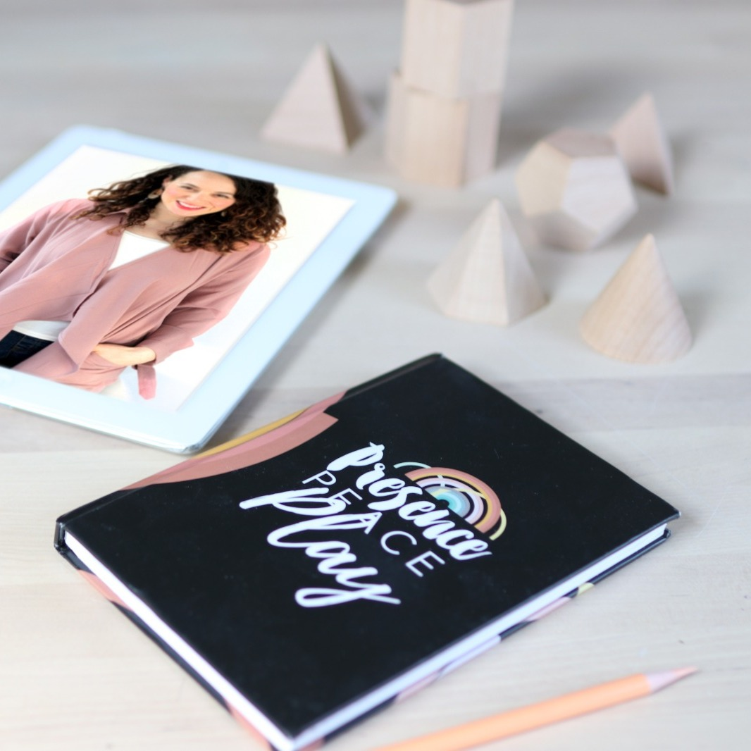 A Journal to help you find ways to deal with stress and on the cover is Peace, Presence Play. There is an iPad in the background with a picture of The Parenting Junkie.
