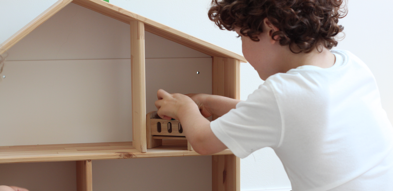 A boy enjoying solitary play with a dollhouse.